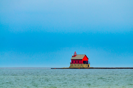 The bright red lighthouse in Grand Haven, Michigan, shown in contrast against dark storm clouds and the blue-green waters of Lake Michigan