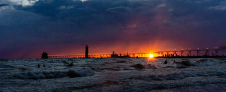 The sun sets below storm clouds behind the lighthouse and catwalk at Grand Haven, Michigan, as a barge enters the Grand River