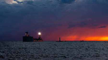 A dramatic sunset and rain storm over Lake Michigan provide a colorful backdrop to a barge sailing past the north pier at Grand Haven, Michigan.