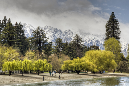 lakefront: Tourists enjoying Queenstown lakefront with snow covered remarkables range in background, new zealand