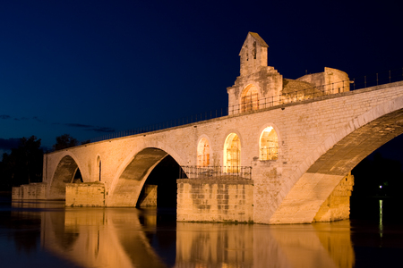 places of interest: Historical Avignon Bridge at night on the Rhone with river and reflection Stock Photo
