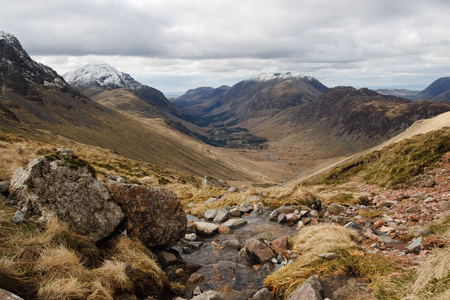 assent: Landscape view of snow capped peaks in the lake district with stream and rocks during an assent of Great Gable