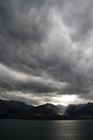 moody: Dark moody sky over mountain range Stock Photo