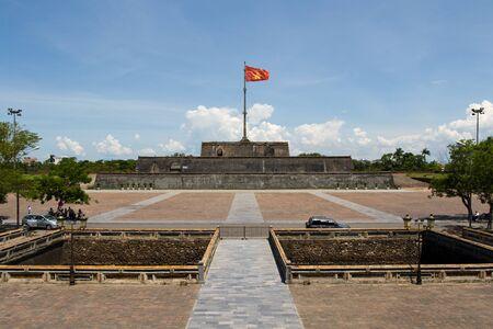 Vietnam flag standing on flag pole above historic Hue Citadel wall