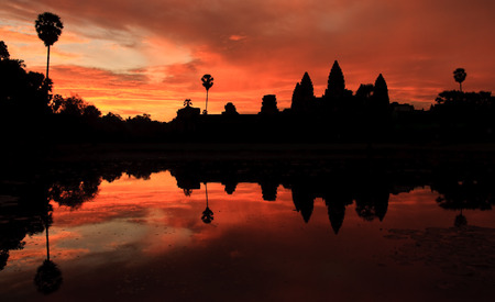 Angkor Wat temple at dramatic sunrise reflecting in water