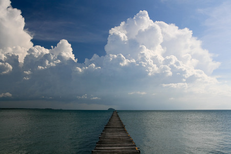 extending: Ocean Pier extending out with stunning cloudy Sky Stock Photo
