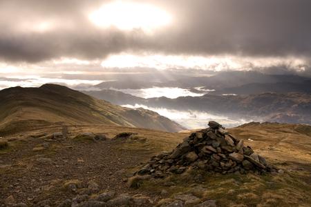 summit lake: Dramatic sun breaks through the cloud over the peak of the fairfield horseshoe summit, Lake District, Cumbria