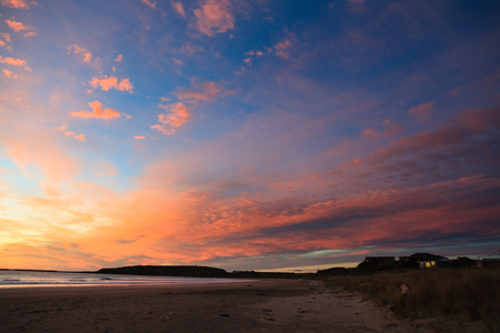 Beautiful cloudscape sunset from the beach across Curio Bay, New Zealand Stock Photo
