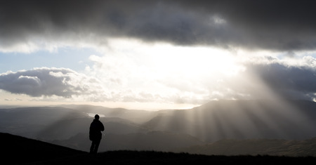 lake district england: Hiker looking at scenic view as sun bursts through clouds, Lake District, England