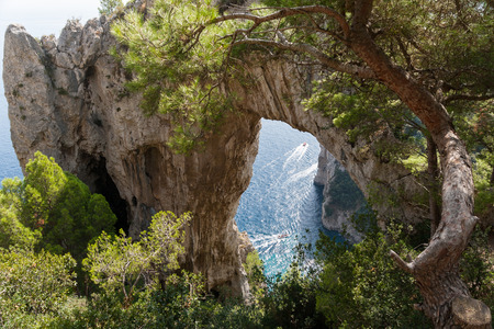 Boats pass under a Natural Arch in Capri, Italy Stock Photo