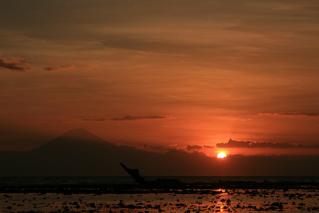 Sunset over Batur Volcano, Bali, seen from the Gilli Islands with shipwreck in foreground
