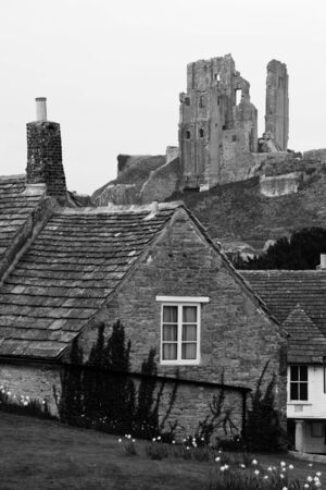 Black and White traditional english villiage with dramatic Corfe Castle Ruin in background Stock Photo