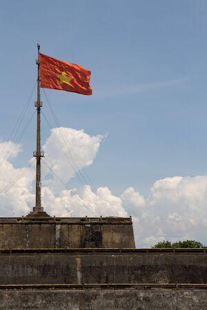 hue: Vietnam flag standing on flag pole above historic Hue Citadel wall