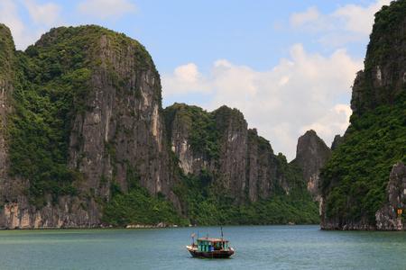 Fishing Boat cruises through the halong bay cliffs, Vietnam
