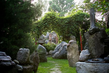 secluded garden with a path surrounded by rocks Фото со стока