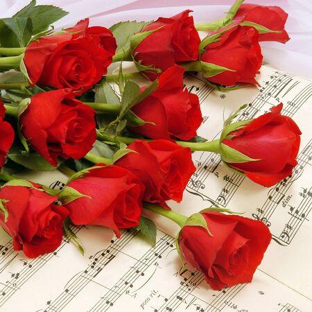 partition musique: Roses rouges sur partition. Banque d'images