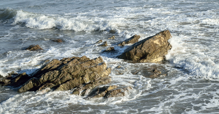 mudstone: Waves breaking over ancient rocks on the coastline. These particular rocks are 350 million years old formed when the world as we know it did not exist.