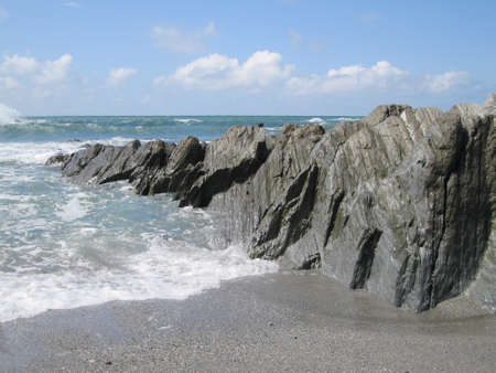 Rocks jutting into sea Stock Photo
