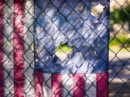 chainlink fence: Tattered American flag hanging on chainlink fence