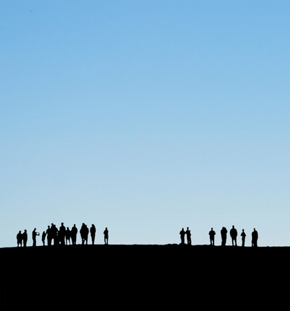 space for type: Group of people on horizon silhouetted against blue sky