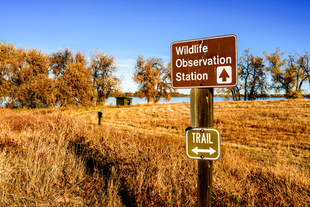 bird watcher: A sign points to a wildlife observation station, the wood hut in the background, at Barr Lake State Park northeast of Denver, Colorado, on a fall morning. A bird watcher contemplates the scene. Stock Photo