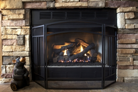 A gas log fireplace provides both emotional and physical warmth as the afternoon sun streams in on a cold winter day.  Stock Photo - 4178585