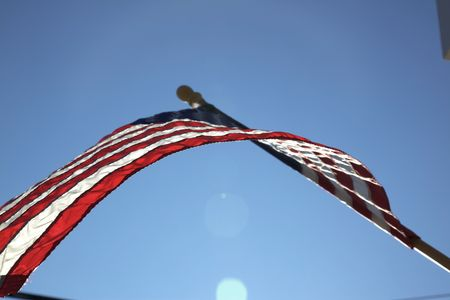 flagpoles: The American flag hangs proudly with a blue sky background on Main Street in Hometown America.
