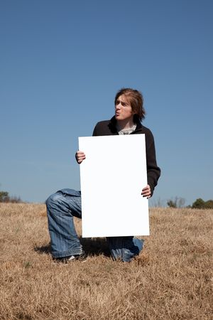 hold up: A 21 year old guy hold up a blank sign that you can use to place your message on. Stock Photo