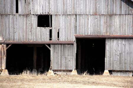 windows and doors: Two Darkened Doors in Old Barn Stock Photo