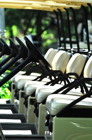 golf cart: Seats and Steering Wheels on a Row of Golf Carts