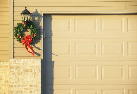 Christmas Wreath by the Garage Door Stock Photo