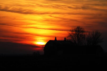 Silhouette of a Barn at Fiery Sunset Stock Photo