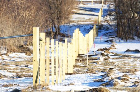 Wooden Fence Under Construction in Winter photo