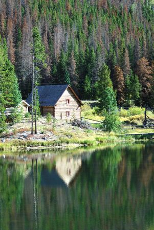 Log Cabin in the Woods by Lake Stock Photo