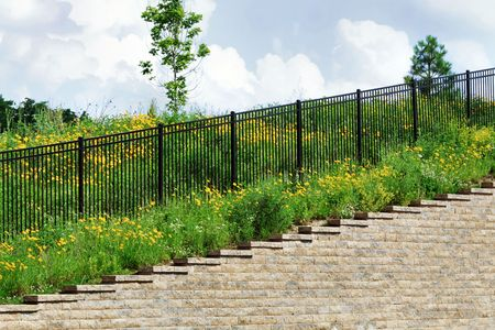 retaining: Black Fence On Top of Retaining Wall Stock Photo