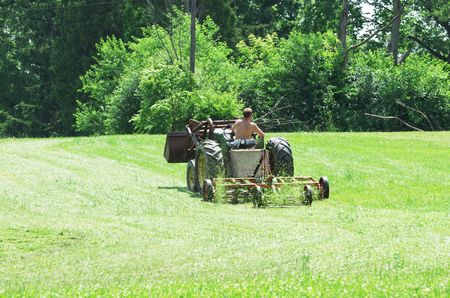 Farmer Mowing Grass with Tractor