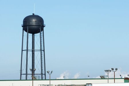 Black Water Tower Over Industrial Plant photo