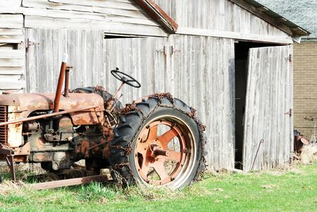 Old Tractor by Weathered Barn Archivio Fotografico