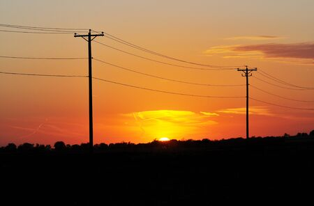 power cables: Sunset Between Power Poles Stock Photo