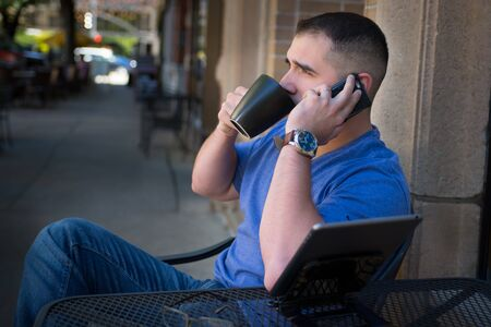 i pad: Handsome young man drinking coffee downtown, with his glasses and tablet on the table, Talking on the phone.