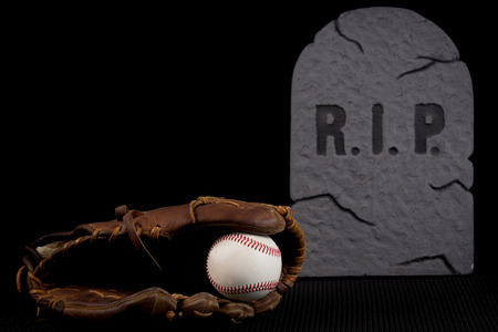 slump: Seasoned leather baseball glove with ball isolated on black background. Bad season or team going through slump.