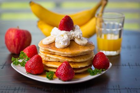 팬케이크, 채찍 크림, 바나나, 사과, 오렌지 주스, 식탁에