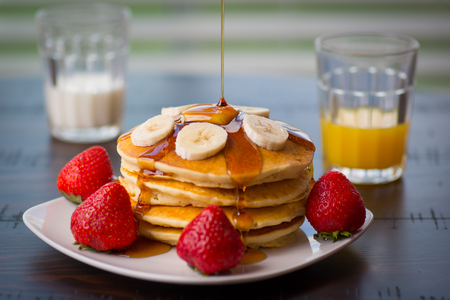 접시에 팬케이크 부풀어 메이플 시럽, 딸기, 바나나, 우유, 오렌지 주스와 부엌에서