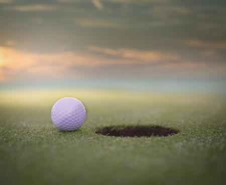 골프 공 구멍 옆에 퍼 팅 그린 골프 코스에 앉아. 아름 다운 석양.