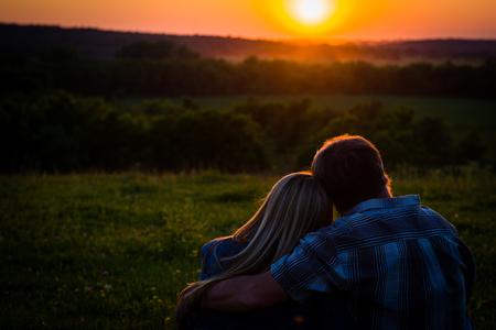 오픈 필드에 앉아 몇, 일몰, 낭만적 인 장면을보고. 나무에 안개와 함께 오렌지 태양입니다.