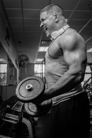 아령 운동으로 운동을하는 남성 체육 보디의 근접 촬영. 헬스 클럽에서 체력 단련 된 몸