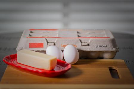 둥근 진한 나무 테이블에 진짜 버터, 달걀 카톤과 버터 접시와 계란.