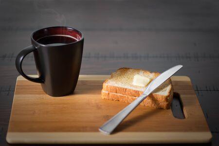 오래 된 나무 라운드 테이블에 버터 토스트와 버터 나이프와 어두운 양조 뜨거운 커피.