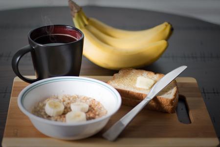 오트밀 죽 바나나, 계 피와 그릇입니다. 토스트와 커피, 버터 나이프와 나무 둥근 테이블에 아침 식사에 대 한 더운 음식과 건강. 스톡 콘텐츠