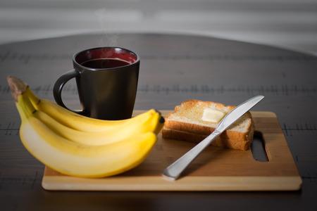바나나와 뜨거운 커피 한잔 어두운 나무 원탁에 토스트. 소박한 스타일. 버터 나이프와 선택적 포커스입니다.